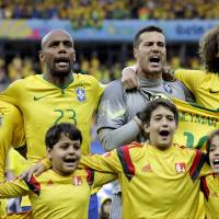 Photo - Brazil's goalkeeper Julio Cesar, second right, and David Luiz, right, hold Neymar's jersey during the playing of the national anthem before the World Cup semifinal soccer match between Brazil and Germany at the Mineirao Stadium in Belo Horizonte, Brazil, Tuesday, July 8, 2014. (AP Photo/Natacha Pisarenko)