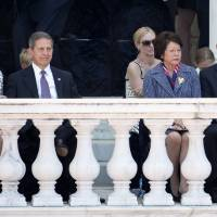 Photo - This photo taken May 26, 2014 shows outgoing Veterans Affairs Secretary Eric Shinseki and his wife Patricia Shinseki, right, and Deputy Veterans Affairs Secretary Sloan D. Gibson and his wife Margaret, left, attending a Memorial Day ceremony at Arlington National Cemetery in Arlington, Va. Gibson has been named to run the Veterans Affairs department on an interim basis while President Obama searches for another secretary after the resignation of Shinseki on Friday. (AP Photo/Jacquelyn Martin)