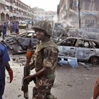 Photo - A Nigerian soldier,  center, walks, at the scene of an  explosion in Abuja, Nigeria, Wednesday, June 25, 2014. An explosion rocked a shopping mall in Nigeria's capital, Abuja, on Wednesday and police say at least over 20 people have been killed and many wounded. Witnesses say body parts were scattered around the exit to Emab Plaza, in the upscale Wuse 11 suburb. (AP Photo/Olamikan Gbemiga)