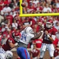 Photo - Oklahoma's Blake Bell (10) passes the ball over Tulsa 's Derrick Alexander (54) during the college football game between the University of Oklahoma Sooners (OU) and the University of Tulsa Hurricanes (TU) at the Gaylord-Family Oklahoma Memorial Stadium on Saturday, Sept. 14, 2013 in Norman, Okla. Photo by Chris Landsberger, The Oklahoman  CHRIS LANDSBERGER