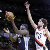 Photo - Memphis Grizzlies forward Zach Randolph, left, drives to the basket past Portland Trail Blazers center Robin Lopez during the first half of an NBA basketball game in Portland, Ore., Tuesday, Jan. 28, 2014. (AP Photo/Don Ryan)