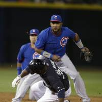 Photo - Seattle Mariners' Abraham Almonte is forced out at second as Chicago Cubs' Emilio Bonifacio watches his throw to first that completed complete a double play during the second inning of a spring exhibition baseball game Wednesday, March 12, 2014, in Peoria, Ariz. (AP Photo/Darron Cummings)