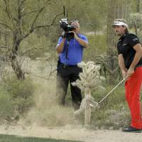 Photo - Victor Dubuisson, of France, hits near a cactus on the 19th hole in his championship match against Jason Day, of  Australia, during the Match Play Championship golf tournament, Sunday, Feb. 23, 2014, in Marana, Ariz. (AP Photo/Ted S. Warren)