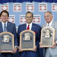 Photo - National Baseball Hall of Fame inductees, from left to right, Tony La Russa, Joe Torre and Bobby Cox hold their plaques after an induction ceremony at the Clark Sports Center on Sunday, July 27, 2014, in Cooperstown, N.Y. (AP Photo/Mike Groll)