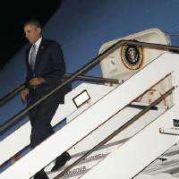 Photo - President Barack Obama walks down the stairs from Air Force One upon his arrival at Fiumicino Airport, Rome, Italy, Wednesday, March 26, 2014. (AP Photo/Pablo Martinez Monsivais)