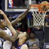 Photo - Memphis Grizzlies forward Ed Davis (32) dunks the ball over Phoenix Suns center Alex Len, right, in the first half of an NBA basketball game, Friday, Jan. 10, 2014, in Memphis, Tenn. (AP Photo/Lance Murphey)