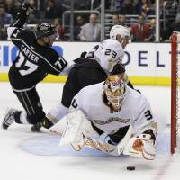 Photo - Anaheim Ducks goalie Viktor Fasth, right, blocks a shot by Los Angeles Kings center Jeff Carter(37) with the help of Francois Beauchemin(22) during the second period of an NHL hockey game in Los Angeles, Monday, Feb. 25, 2013. (AP Photo/Chris Carlson)