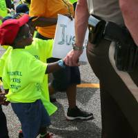 Photo - St. Louis County Police Sgt. Colby Dolly joins hands with five-year-old Zion King Frenchie during a march with members of the St. Louis chapters of the NAACP and the National Urban League on West Florissant Avenue in Ferguson, Mo., on Saturday, Aug. 23, 2014. Ferguson's streets remained peaceful as tensions between police and protesters continued to subside after nights of violence and unrest that erupted when Officer Darren Wilson, a white police officer, fatally shot Michael Brown, an unarmed black 18-year-old. (AP Photo/St. Louis Post-Dispatch, Robert Cohen)
