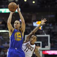 Photo - Golden State Warriors' Stephen Curry (30) shoots a three-point basket as Milwaukee Bucks' Monta Ellis (11) defends during the first half of an NBA basketball game on Saturday, Jan. 26, 2013, in Milwaukee. (AP Photo/Jim Prisching)