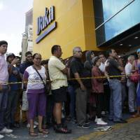 Photo - Shoppers wait outside to come in a Daka appliance store in Caracas, Venezuela, Saturday, Nov. 9, 2013. In a bid to bring down prices that have jumped in tandem with demand for dollars on the black market, Venezuela's President Nicolas Maduro on Wednesday tightened controls on currency transactions. With hard-fought municipal elections approaching next month, he also ordered the military to shut down businesses found hoarding products or speculating on prices.  (AP Photo/Ariana Cubillos)
