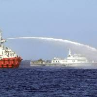Photo - In this photo released by Vietnam Coast Guard, a Chinese ship, left, shoots water cannon at a Vietnamese vessel, right, while a Chinese Coast Guard ship, center, sails alongside in the South China Sea, off Vietnam's coast, Wednesday, May 7, 2014. Chinese ships are ramming and spraying water cannons at Vietnamese vessels trying to stop Beijing from setting up an oil rig in the South China Sea, according to Vietnamese officials and video evidence Wednesday, a dangerous escalation of tensions in disputed waters considered a global flashpoint. (AP Photo/Vietnam Coast Guard)