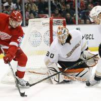 Photo - Detroit Red Wings center Tomas Tatar (21), of the Czech Republic, takes a shot against Anaheim Ducks goalie Viktor Fasth (30), of Sweden, and defenseman Toni Lydman (32), of Finland, in the second period of an NHL hockey game on Friday, Feb. 15, 2013, in Detroit. (AP Photo/Duane Burleson)