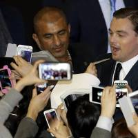 Photo - Actor Leonardo DiCaprio signs autographs for fans during the premiere of his new film