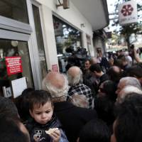 Photo - FILE - In this Thursday, March 28, 2013 file photo, people wait outside a branch of Laiki Bank in Nicosia. Engineering a financial bailout for Cyprus in March 2013 was such a chaotic process that top European officials say it is time to rethink how the region manages its crisis _ and who should be involved. Officials say the International Monetary Fund, which has contributed financial expertise and billions in emergency loans, may no longer be needed as a key decision-making partner. And they say that the eurozone would be able to make decisions and take action more quickly if it wasn't bound by the need for unanimous agreement among its 17 member countries.  (AP Photo/Petros Giannakouris, File)