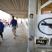 Photo - OPEN CARRY LAW: A no firearms sign hangs on the door at the Goodwill store at 15th and Broadway in Edmond, Monday  November 19, 2012. Photo By Steve Gooch, The Oklahoman