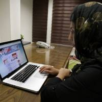 Photo -   Iranian photojournalist Maryam Rahmanian checks the newly launched website of Iran's Intelligence Ministry, in Tehran, Iran, Wednesday, Oct. 10, 2012. A glimpse into the shadow world of Iran's main spy agency is now a click away. In an unexpected display of outreach, the Intelligence Ministry now hosts a website with addresses of provincial offices, appeals for tips and anti-American essays that mock rising obesity rates, large prison populations and school shootings. (AP Photo/Vahid Salemi)