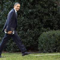 Photo - President Barack Obama looks to the media as he walks to the Oval Office of the White House as he returns from greeting members of the staff, Tuesday, Dec. 18, 2012, in Washington. (AP Photo/Carolyn Kaster)