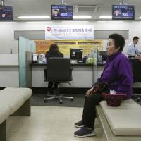 Photo - A customer sits in a branch of Shinhan Bank in Seoul, South Korea, while the bank's computer networks are paralyzed Wednesday, March 20, 2013. Police and South Korean officials were investigating the simultaneous shutdown Wednesday of computer networks at several major broadcasters and banks. While the cause wasn't immediately clear, speculation centered on a possible North Korean cyberattack. (AP Photo/Ahn Young-joon)