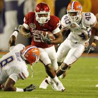 Photo - BOWL CHAMPIONSHIP SERIES / BOWL GAME: University of Oklahoma's Chris Brown (29) rushes past Florida's Carlos Dunlap (8) and Brandon Hicks (40) during the first half of the BCS National Championship college football game between the University of Oklahoma Sooners (OU) and the University of Florida Gators (UF) on Thursday, Jan. 8, 2009, at Dolphin Stadium in Miami Gardens, Fla.   PHOTO BY NATE BILLINGS, THE OKLAHOMAN ORG XMIT: KOD