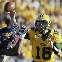 Photo - FILE - IN this Jan. 4, 2014 file photo, North Dakota State quarterback Brock Jensen gets a pass off under pressure from Towson defensive end Ryan Delaire during the FCS championship NCAA college football game  in Frisco, Texas. NDSU won 35-7. Jensen, who is the winningest quarterback in NCAA Football Championship Subdivision history, is gearing up for his pro day in Fargo on Wednesday, March 12, 2014, after being overlooked for the NFL combine. (AP Photo/Tony Gutierrez, File)