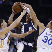 Photo - Oklahoma Thunder guard Russell Westbrook (0) shoots between Golden State Warriors' Klay Thompson, left, and Stephen Curry (30) during the first half of an NBA basketball game Thursday, April 11, 2013, in Oakland, Calif. (AP Photo/Ben Margot) ORG XMIT: OAS101