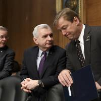 Photo - In this Feb. 27, 2014, file photo, Sen. Jack Reed, D-R.I., center, confers with Sen. Dean Heller, R-Nev., right, with Sen. Robert Menendez, D-N.J., at far left, as members of the Senate Banking Committee gather for an appearance by Janet Yellen on Capitol Hill in Washington. One partisan election-year battle that senators seem likely to resolve when they return from recess later this month is the fight over renewing expired benefits for the long-term unemployed. Reed, a leading bargainer, said the March 13 agreement would help families and