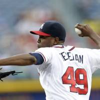 Photo - Atlanta Braves starting pitcher Julio Teheran (49) throws against the Minnesota Twins in the first inning of a baseball game Monday, May 20, 2013, in Atlanta. (AP Photo/John Bazemore)