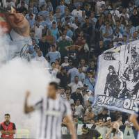 Photo - Lazio fans, background, react as Juventus' Carlos Tevez, of Argentina, center, celebrates his goal during the Italian Supercup soccer match at the Rome Olympic stadium Sunday, Aug. 18, 2013. (AP Photo/Gregorio Borgia)