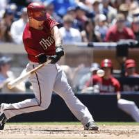 Photo - Arizona Diamondbacks' Tuffy Gosewisch drives a single up the middle to bring in two unearned runs against the San Diego Padres during the fourth inning of a baseball game on Sunday, May 4, 2014, in San Diego.  (AP Photo/Lenny Ignelzi)