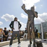Photo - Washington Redskins quarterback Robert Griffin III looks at a bronze statute of himself after it was unveiled outside the new McLane Stadium before an NCAA college football game between SMU and Baylor Sunday, Aug. 31, 2014, in Waco, Texas. Griffin won the Heisman Trophy when he played at Baylor. (AP Photo/LM Otero)