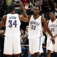 Photo - CELEBRATION: Oklahoma City's Desmond Mason (34), Jeff Green (22) and Kevin Durant (35) celebrate late in the fourth quarter of the NBA basketball game between the Toronto Raptors and the Oklahoma City Thunder at the Ford Center in Oklahoma City, Friday, Dec. 19, 2008. The Thunder won, 91-83. BY NATE BILLINGS, THE OKLAHOMAN ORG XMIT: KOD