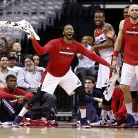 Photo - Washington Wizards guard John Wall, left, with forward Trevor Booker and center Marcin Gortat, right, from Poland, celebrate near the bench in the second half of an NBA basketball game against the Boston Celtics on Wednesday, April 2, 2014, in Washington. The Wizards won 118-92, and clinched a playoff berth. (AP Photo/Alex Brandon)