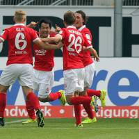 Photo - Mainz's  Shinji Okazaki , second left, celebrates the opening goal during the German Bundesliga soccer match between SC Paderborn and. FSV Mainz 05 in Paderborn, Germany,  Sunday Aug. 24, 2014.  Mainz earned a 2-2 draw at promoted Paderborn with an injury time penalty to deny the home side a victory in its first Bundesliga game on Sunday.  (AP Photo/dpa, Oliver Krato)