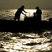 Photo - Striper anglers try their luck in the early morning hours as the sun rises over Lake Texoma. Photo by Bryan Terry, The Oklahoman Archive