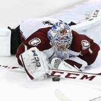 Photo - Colorado Avalanche goalie Semyon Varlamov (1) dives on a loose puck during the third period of an NHL hockey game against the Chicago Blackhawks Tuesday, March 4, 2014, in Chicago. The Avalanche won 4-2. (AP Photo/Charles Rex Arbogast)