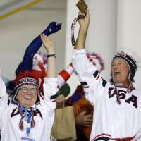 Photo - USA fans cheers during the 2014 Winter Olympics women's ice hockey game between Canada and the United States at Shayba Arena, Wednesday, Feb. 12, 2014, in Sochi, Russia. (AP Photo/Matt Slocum)