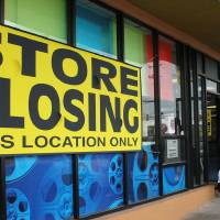Photo - Customers leave the Blockbuster store at NW 23 and N Flynn Avenue in Oklahoma City which is closing.  Tiffany Gibson - THE OKLAHOMAN