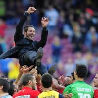 Photo - Players throw in the air Atletico's coach Diego Simeone from Argentina after a Spanish La Liga soccer match between FC Barcelona and Atletico Madrid at the Camp Nou stadium in Barcelona, Spain, Saturday, May 17, 2014. Atletico clinched its first league title in 18 years after a 1-1 draw. (AP Photo/Manu Fernandez)