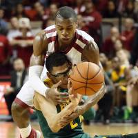 Photo - Baylor's Isaiah Austin (21) passes the ball away from Oklahoma's Buddy Hield (24) during an NCAA men's college basketball game between Baylor and the University of Oklahoma at Lloyd Noble Center in Norman, Okla., Saturday, Feb. 8, 2014. OU won, 88-72. Photo by Nate Billings, The Oklahoman