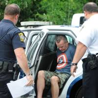 Photo - James Lacroix, 53, is led from a police cruiser into Barnstable District Court in Barnstable, Mass. Wednesday, July 16, 2014. Lacroix, accused of breaking into a home once owned by John F. Kennedy, told authorities he was looking for singer Katy Perry. (AP Photo/Cape Cod Times, Steve Heaslip)
