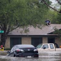 Photo - A man sits on top of a home on Buttonbush Drive in southeast Austin, Texas, on Thursday, Oct. 31, 201 Heavy overnight rains brought flooding to the area. The National Weather Service said more than a foot of rain fell in Central Texas, including up to 14 inches in Wimberley, since rainstorms began Wednesday.  (AP Photo/The Austin American-Statesman, Deborah Cannon) AUSTIN CHRONICLE OUT, COMMUNITY IMPACT OUT, INTERNET MUST CREDIT PHOTOGRAPHER AND STATESMAN.COM, NO SALES