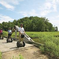 Photo -   This July 2012 photo provided by Kingsmill Resort shows Kingsmill Resort's director of sports, Kevin Dry, leading a Segway tour on the resort's grounds in Williamsburg, Va. A number of hotels offer Segway tours as a novel way to see their grounds and nearby scenic areas. (AP Photo/Kingsmill Resort)