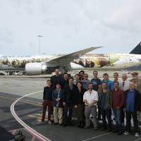 Photo -   This photo released by Air New Zealand shows cast and crew including Peter Jackson, front center, posing for a photo in front of a 777-300 aircraft decorated with scenes and characters from the soon to be released,