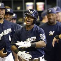 Photo - Milwaukee Brewers' Jean Segura, center, celebrates in the dugout after hitting a home run during the fifth inning of a baseball game against the Atlanta Braves, Friday, June 21, 2013, in Milwaukee. (AP Photo/Morry Gash)
