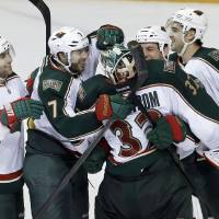 Photo - Minnesota Wild goalie Niklas Backstrom (32), of Finland, is congratulated by Jason Zucker (16), Matt Cullen (7), Zenon Konopka, second from right, and Devin Setoguchi (10) after the Wild beat the Nashville Predators 2-1 in a shootout at an NHL hockey game on Saturday, March 9, 2013, in Nashville, Tenn. (AP Photo/Mark Humphrey)