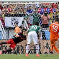 Photo - Mexico's goalkeeper Guillermo Ochoa can not stop a penalty shot by Netherlands' Klaas-Jan Huntelaar to score his side's second and winning goal during the World Cup round of 16 soccer match between the Netherlands and Mexico at the Arena Castelao in Fortaleza, Brazil, Sunday, June 29, 2014. The Netherlands defeated Mexico 2-1. (AP Photo/Felipe Dana)