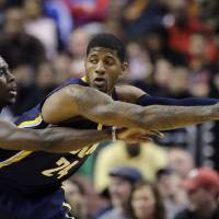 Photo - Indiana Pacers' Paul George, right, tries to keep the ball away from Philadelphia 76ers' Jrue Holiday during the first half of an NBA basketball game on Saturday, March 16, 2013, in Philadelphia. (AP Photo/Matt Slocum)