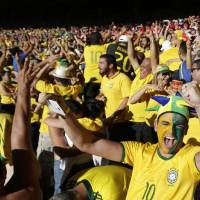 Photo - Brazil soccer fans celebrate their team's victory over Chile after a penalty shootout at a World Cup round of 16 match at Mineirao Stadium in Belo Horizonte, Brazil, Saturday, June 28, 2014. Brazil won 3-2 on penalties after the game ended 1-1. (AP Photo/Petr David Josek)
