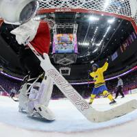 Photo - Goalkeeper Florence Schelling of Switzerland takes the puck out of the net after Michelle Lowenhielm of Sweden, not shown, during the women's bronze medal ice hockey game at the 2014 Winter Olympics, Thursday, Feb. 20, 2014, in Sochi, Russia. (AP Photo/Martin Rose, Pool)
