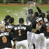 Photo - Miami Marlins' Jeff Baker, center, is sprayed with water by Marcell Ozuna (13) after driving in the winning run with a single to score Adeiny Hechavarria in the ninth inning during a baseball game against the Washington Nationals, Monday, July 28, 2014, in Miami. The Marlins defeated the Nationals 7-6. (AP Photo/Lynne Sladky)